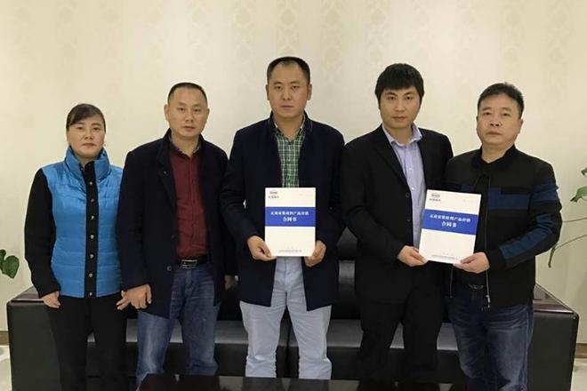 川渝省区经理康能(右二)与经销商何松文(中)签约合影